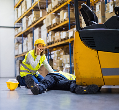 worker-calling-for-help-kneeling-over-colleague-on-floor-who-has-been-runover-by-a-forklift