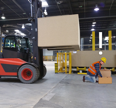 man-crouching-opening-box-in-front-of-approaching-forklift